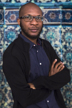 "HEBRON - WEST BANK -  JUNE 3:  Nigerian-American writer Teju Cole poses for a portrait inside the Ibrahimi mosque or Tomb of the Patriarchs during a 2014 Palestine Festival of Literature tour on June 3, 2014 in Hebron, West Bank.  The festival is an annual event that aims to bring a cultural festival of international standard to audiences in Palestine to assert ""the power of culture over the culture of power.""  (Photo by Rob Stothard/Getty Images)"