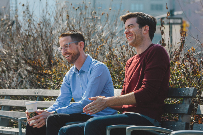 "Comedians Neal Brennan, left, and John Mulaney, right, sit on a park bench in Tribeca on March 9th, 2016. Brennan is currently doing a solo show called ""3 Mics""."